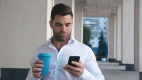 Sms молодого человека отправляя SMS используя приложение по умному телефону в городе около buildung офиса Кофе красивого молодого акции видеоматериалы