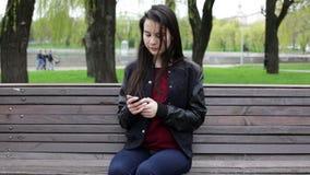 Sms молодой женщины брюнет отправляя СМС на мобильном телефоне видеоматериал