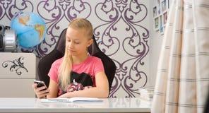 Sms сочинительства девушки школы на smartphone Стоковые Изображения