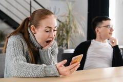 SMS 看电话的特写镜头画象滑稽的震惊急切害怕的少女看坏消息照片消息与 免版税图库摄影
