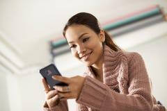 Sms asiatiques de lecture de fille sur le smarthphone Image libre de droits