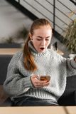 SMS. Closeup portrait funny shocked anxious scared young girl looking at phone seeing bad news photos message with stock photos