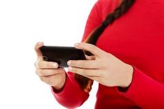 Sms d'écriture de jeune femme sur le smartphone Image stock