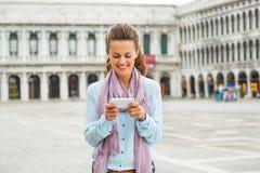 Sms da escrita da mulher no marco de san da praça em Veneza Foto de Stock Royalty Free