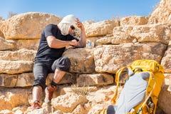 Sms de assento do telefone da mensagem do indivíduo ao descansar o curso do deserto fotografia de stock