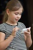 Sms de dactilografia da menina em um smartphone Imagem de Stock