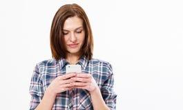 Sms de datilografia da menina feliz no espaço branco da cópia do fundo, imagem de uma mulher moreno de sorriso que usa o smartpho imagens de stock royalty free