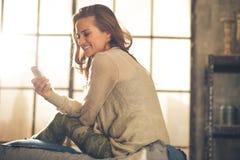 SMS de la escritura de la mujer joven en el apartamento del desván Fotos de archivo libres de regalías