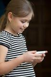 SMS de la lectura de la niña en el teléfono foto de archivo