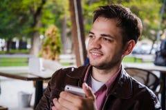 SMS del hombre de Smartphone que manda un SMS en el café al aire libre en terraza en verano Adulto joven urbano casual feliz que  Imagenes de archivo