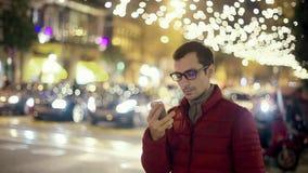 SMS del hombre que manda un SMS usando el App en el teléfono elegante en la ciudad almacen de metraje de vídeo