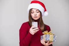 SMS del texto de la mujer con el sombrero de la Navidad Imagen de archivo libre de regalías