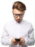 Sms di battitura a macchina del giovane uomo d'affari allegro sul suo telefono cellulare Immagini Stock