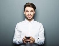Sms di battitura a macchina del giovane uomo d'affari allegro sul suo telefono cellulare Fotografie Stock