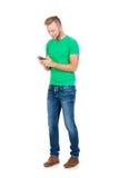 Sms di battitura a macchina dell'adolescente con uno smartphone su bianco Fotografie Stock Libere da Diritti