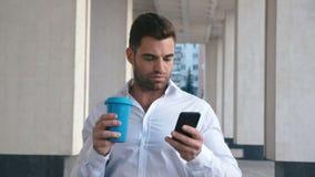 Sms do homem novo que texting usando o app no telefone esperto na cidade perto do buildung do escritório caf? bebendo do homem de filme