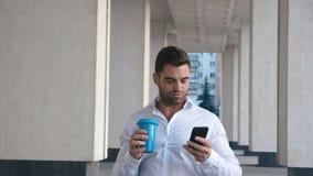 Sms do homem novo que texting usando o app no telefone esperto na cidade perto do buildung do escritório caf? bebendo do homem de vídeos de arquivo