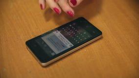 Sms för kvinnatelefonhandstil på smartphonen på tabellen lager videofilmer