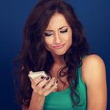 Sms för ung kvinna för misslynt surprisung grimacing läs- på mobilen ph Royaltyfri Bild