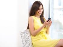 Sms heureux de lecture de femme à son téléphone portable image libre de droits