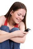 SMS joy. Beautiful girl sending a message by cell phone, isolated on white Stock Photo
