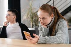 SMS Lustiges entsetztes besorgtes erschrockenes junges Mädchen des Nahaufnahmeporträts, welches das Telefon sieht Fotomitteilung  lizenzfreies stockfoto