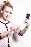 Sms mandanti un sms della lettura della donna di affari sullo smartphone Immagine Stock Libera da Diritti