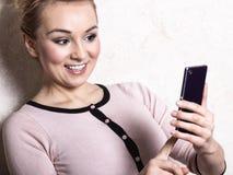 Sms mandanti un sms della lettura della donna di affari sullo smartphone Fotografie Stock Libere da Diritti