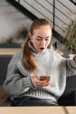 SMS Moça assustado ansiosa chocada engraçada do retrato do close up que olha o telefone que vê a mensagem das fotos das más notíc fotos de stock
