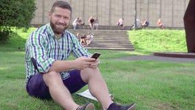 Sms no smartphone, sorrisos da escrita do homem novo para a câmera steadicam video estoque