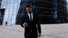 Sms ou mensageiro considerável da leitura do empresário que usa o app no iphone no centro de negócio video estoque