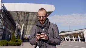SMS que manda un SMS caucásico del hombre joven usando el app en el teléfono elegante en ciudad El hombre de negocios joven hermo metrajes