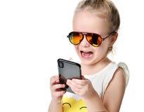 SMS que manda un SMS de la lectura de la chica joven en el móvil del teléfono móvil con la pantalla táctil en gafas de sol Imágenes de archivo libres de regalías