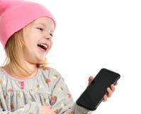 SMS que manda un SMS de la lectura del niño de la muchacha en el móvil del teléfono móvil con la risa feliz de la pantalla táctil Imágenes de archivo libres de regalías