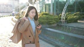 SMS que manda un SMS de la muchacha asiática atractiva en el teléfono móvil metrajes