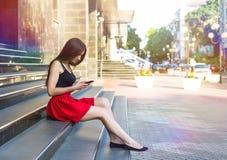 SMS que manda un SMS de la mujer caucásica feliz joven en la ciudad al aire libre Relaje el concepto del verano de la forma de vi Imagenes de archivo