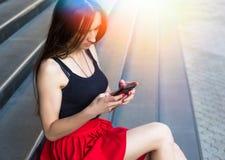 SMS que manda un SMS de la mujer caucásica feliz joven en la ciudad al aire libre Relaje el concepto del verano de la forma de vi Imagen de archivo