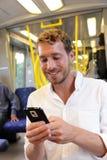 SMS que manda un SMS del hombre de negocios del subterráneo en el smartphone app Fotografía de archivo