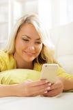 SMS que mecanografía del adolescente joven y hermoso usando un smartphone Fotografía de archivo