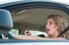 SMS que pulsa mientras que conduce el coche Imágenes de archivo libres de regalías
