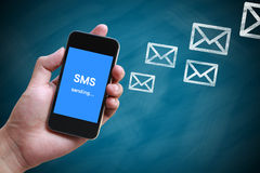 SMS sending. Text on phone screen in hand with chalkboard background Royalty Free Stock Images