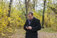 SMS sonriente de la lectura del hombre joven en el teléfono Un hombre comprueba el correo en el teléfono Imágenes de archivo libres de regalías