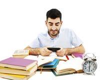 SMS sonriente de la lectura del hombre joven en móvil en vez de hacer la preparación Foto de archivo