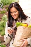 SMS sonriente del teléfono móvil de las verduras de las compras de la mujer imagen de archivo