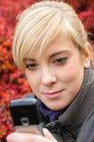 Sms texting attraenti della giovane donna Fotografie Stock Libere da Diritti