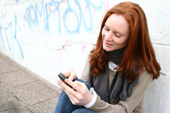 SMS Texting in the City. A young Caucasian female with red hair posing next to a graffiti wall in an urban setting and writing a text message on her mobile phone Stock Images