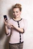 Sms texting da leitura da mulher de negócios no smartphone Fotos de Stock Royalty Free