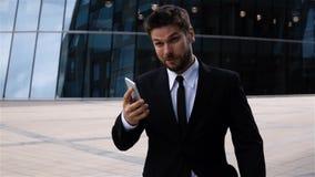 Sms texting do homem de negócios novo usando o app no telefone esperto ao andar na cidade vídeos de arquivo