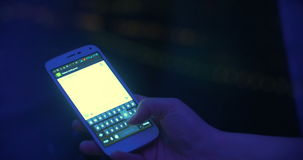 Sms typing by the window at night. Close-up shot of a female hand typing sms or email on smart phone on the background of distant city lights at night. At first stock video footage