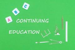 Smsa att fortsätta utbildning, från ovannämnda träminituresskolatillförsel och abc-bokstäver på grön bakgrund Royaltyfria Foton
